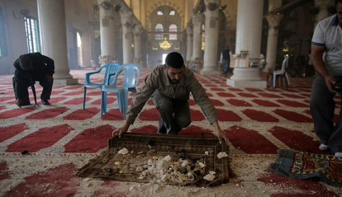 Palestinians clean the Al Aqsa mosque after clashes with Israeli police in Jerusalem's Old City